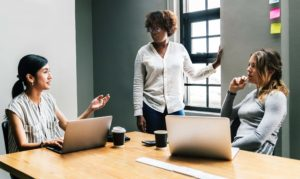 three female business professionals in a meeting
