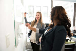 two female employees writing on dry erase board
